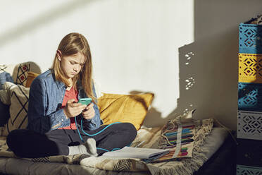 Girl sitting on bed at home doing homework and using smartphone - MCF00705