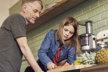 Father and daughter in kitchen preparing fruit and vegetables - MCF00717