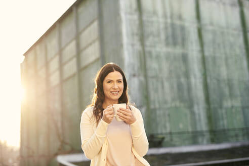 Portrait of smiling mature businesswoman having coffee while sitting on terrace during sunny day - MMIF00200