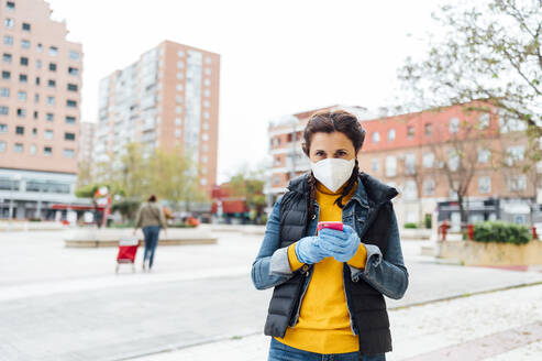 Woman wearing protective mask and using smartphone on square - JCMF00588