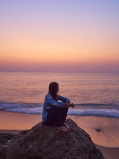 Woman sitting on a rock watching sunset at seafront, Angola - VEGF01942