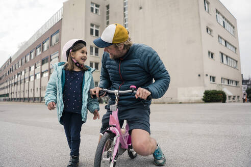 Happy father with daughter on her bicycle - JOSEF00279