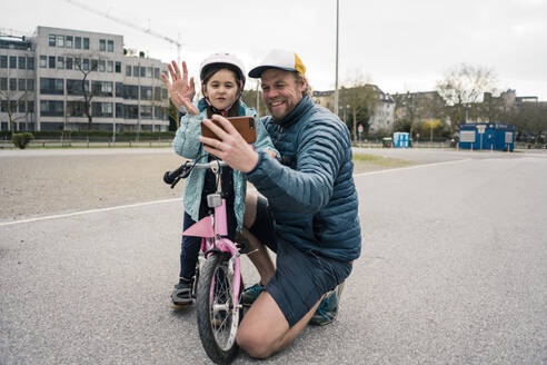 Happy father and daughter with bicycle taking a selfie - JOSEF00288