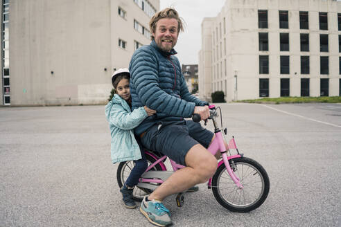 Playful father with daughter on her bicycle - JOSEF00291