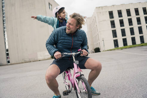 Playful father with daughter on her bicycle - JOSEF00294