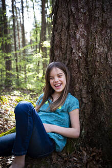 Portrait of laughing girl leaning against tree trunk in forest - LVF08840