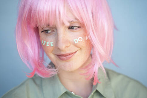 Young woman wearing pink wig, letters on her face, freedom - AFVF06106