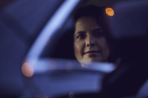 Reflection of woman in rear-view mirror of a car at night - MCF00728