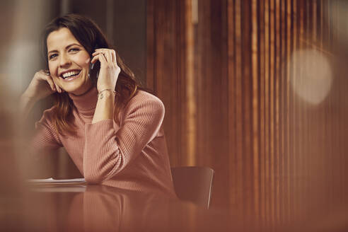 Laughing businesswoman on the phone sitting at desk in office - MCF00758
