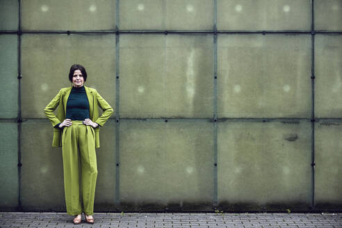 Portrait of confident businesswoman wearing green suit standing at a wall - MCF00767
