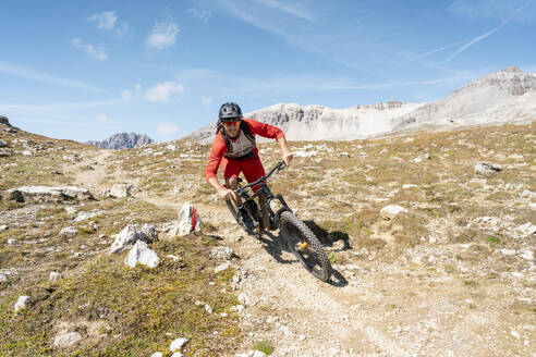 Man riding on mountainbike, Munestertal Valley, Grisons, Switzerland - HBIF00103