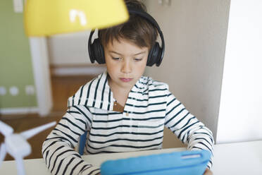 Boy doing homeschooling and using tablet and headphones at home - HMEF00895
