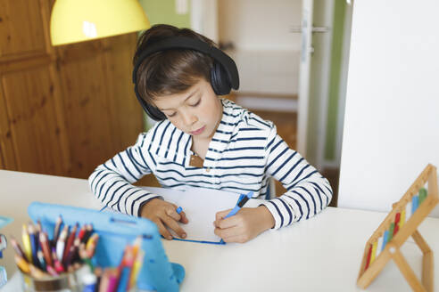 Boy doing homeschooling and writing on notebook, using tablet and headphones at home - HMEF00898
