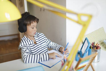 Boy doing homeschooling and writing on notebook, using tablet and headphones at home - HMEF00901