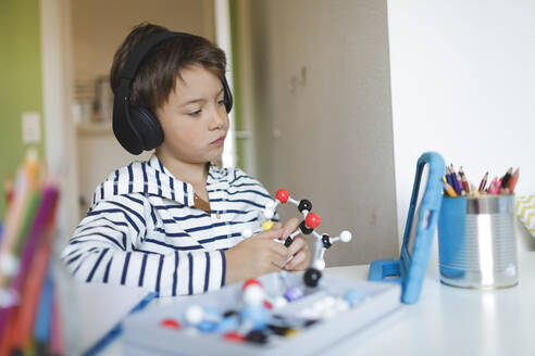 Boy doing homeschooling and holding molecule model, using tablet and headphones at home - HMEF00904