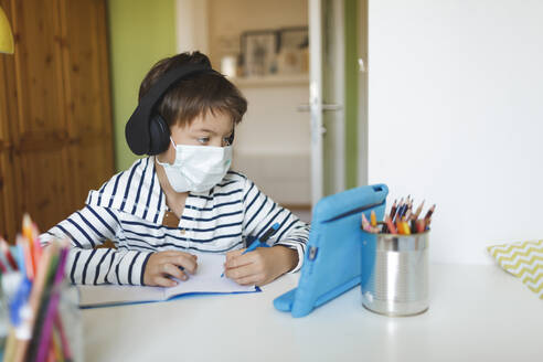 Boy doing homeschooling and writing on notebook, using tablet and headphones, wearing mask at home during corona crisis - HMEF00907