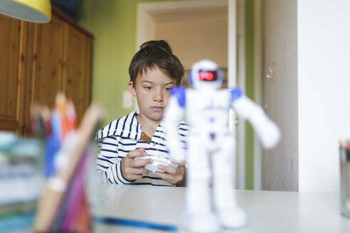 Boy playing with his remote-controlled toy robot at home - HMEF00910