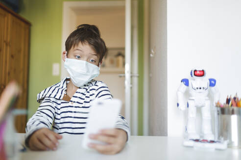 Boy doing homeschooling and using smartphone wearing mask at home during corona crisis - HMEF00913