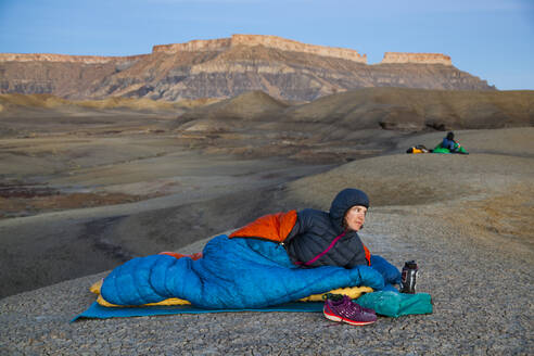 People watch sunrise from camp in Factory Butte badlands, Utah - CAVF79104