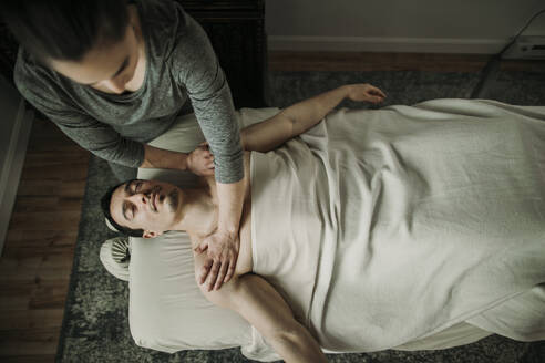 Female massage therapist applies pressure to male's shoulders - CAVF79242