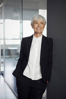Portrait of smiling senior businesswoman leaning against wall in an office looking at distance - RBF07590