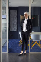 Portrait of fashionable senior businesswoman wearing black pantsuit in office - RBF07602