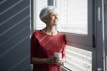 Portrait of happy senior woman with coffee mug looking out of window - RBF07608