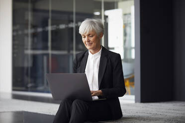 Portrait of senior businesswoman working on laptop - RBF07611