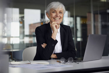 Portrait of relaxed senior businesswoman at desk in her office - RBF07614