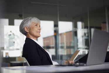 Senior businesswoman sitting at desk in office looking at distance - RBF07617