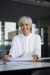 Portrait of smiling senior businesswoman at desk in her office - RBF07620