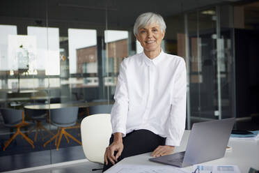 Portrait of smiling senior businesswoman sitting on desk in her office - RBF07626