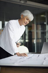 Portrait of architect working on construction plan in office - RBF07629