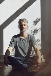 Portrait of mature man sitting on the floor at home meditating - MCF00778