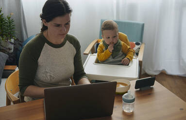 Woman working on laptop at home while her little son watching movies on mobile phone - BZF00546