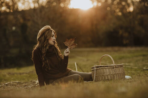 Fashionable woman with basket and autumn leaf sitting on a meadow at backlight - GMLF00076