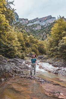 Spain, Province of Huesca, Portrait of female hiker posing over clear mountain river - FVSF00204