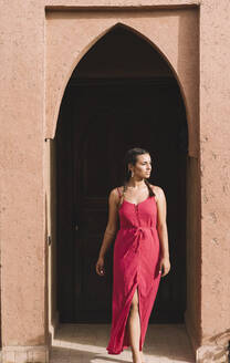 Portrait of young woman in front of entrance door, Merzouga, Morocco - DAMF00386