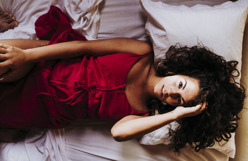 Portrait of young woman wearing red dress lying on bed, top view - DAMF00392