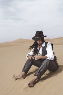 Fashionable young woman sitting barefoot on dune looking at pocket watch, Merzouga desert, Morocco - DAMF00395