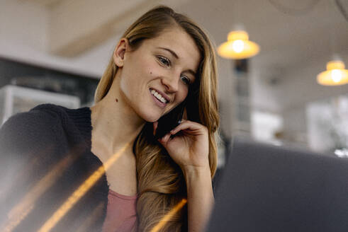 Smiling young woman using smartphone and laptop in a cafe - GUSF03523