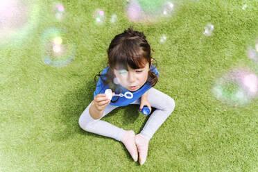 Portrait of little girl blowing soap bubbles - GEMF03604