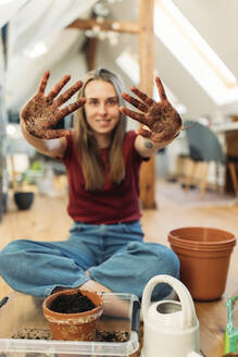 Young woman planting on wooden floor shwin her dirty hands - GUSF03557