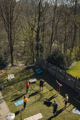 Group of friends doing workout together in garden - GUSF03596