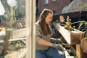 Young woman working in garden in sunshine - GUSF03605