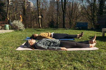 Two women lying on gym mats in garden - GUSF03683