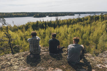 Friends sitting on hill, looking at lake, Nykoping, Sweden - GUSF03698