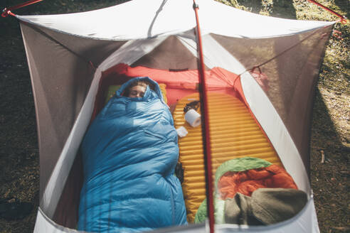 Young woman sleeping in sleeping bag in a tent - GUSF03701
