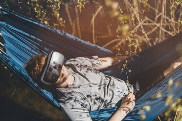 Young man relaxing in hammock, using VR glasses - GUSF03704