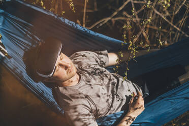 Young man relaxing in hammock, VR glasses on his forehead - GUSF03707